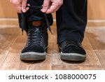 a man ties up his shoelaces on... | Shutterstock . vector #1088000075