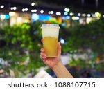 holds plastic glass of iced... | Shutterstock . vector #1088107715