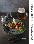 Small photo of Meat steak with butter, salad, pita pita on wooden black background