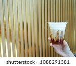 hand holding plastic glass of... | Shutterstock . vector #1088291381