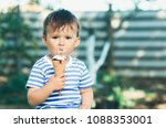 a child in a t shirt on a bench ... | Shutterstock . vector #1088353001