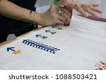 Small photo of The process of creating a picture on the fabric. The hands of a talented artist create a pattern.