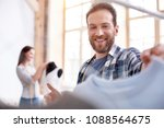 Small photo of Fashion look. Low angle of cheerful male stylist choosing garment while looking down