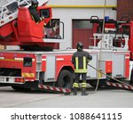 Small photo of big red fire engine with aerial ladder and firefighters during an emergency