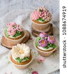 Small photo of Cupcakes decorated with cream flowers: roses, peonies, chrysanthemums, poppies, scabiosa, on a wooden background with a lacy napkin