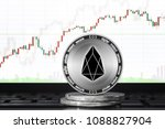 EOS coin; EOS cryptocurrency on the background of the trading chart