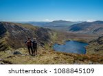 Two hikers with backpacks stand at the head of two trails on the Carneddau Mountains in Snowdonia, Wales, and consider their route. One trail leads high onto a ridge, the other leads down to a lake.
