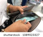 Small photo of Close up the hands of women hold money in the wallet to pay bills at counter.Ringgit Malaysia bank note fifty ringgit Malaysia