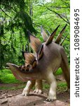 Small photo of Szklarska Poreba, Poland - May 10, 2018: Stegosaurus model standing in a forest on the Dino Park