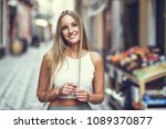 smiling young woman in urban... | Shutterstock . vector #1089370877