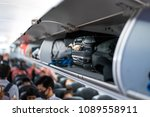 luggage on airplane shelf... | Shutterstock . vector #1089558911