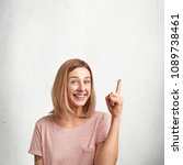 Small photo of Attractive Caucasian lovely woman with bobbed hairdo, raises hand and points upwards, being excited with excellent news, stands against white concrete wall, copy space for your promotional text