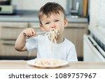 baby fork greedily eats pasta... | Shutterstock . vector #1089757967