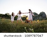 young girls in white shirts and wreaths of flowers on the background of a fire. The celebration of the pagan Slavic holiday of Ivan Kupala Day or Midsummer.