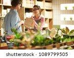 happy shop assistant giving... | Shutterstock . vector #1089799505