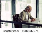 Small photo of close up side view photo of mature grey-haired businessman working in the modern office with panorama window. read book with pen. underline interesting moments in poem