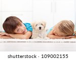 Kids at home with their new pet - a fluffy white dog - stock photo