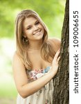 Closeup portrait of beautiful young girl smiling in the park - stock photo