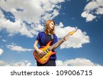 Redhead girl with guitar at sky background. - stock photo