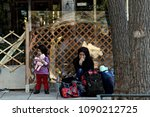 a migrant woman sits with... | Shutterstock . vector #1090212725