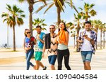 Small photo of Happy friends on seaside walk in Barcelona. Multiracial group of best friends enjoying summer and time together. Happiness and friendship during a travel in Spain