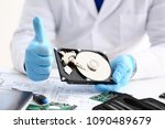 Small photo of Male repairman wearing blue gloves is holding hard drive from computer laptop in hands show OK thumbs up. Performs diagnostics performs urgent repairs recovery of lost data during deletion HDD closeup