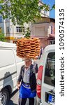 Small photo of Istanbul, Turkey - April 28th 2018: Old man with plate ful of bagels on his head selling on the street