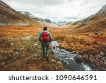 Traveling Man tourist with backpack hiking in mountains landscape active healthy lifestyle adventure vacations in Scandinavia - stock photo