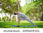 Small photo of Inspired Indian man doing yoga asanas in city park. Young citizen exercising outside and standing in yoga side angle pose. Fitness outdoors and life balance concept