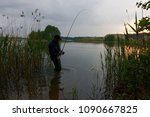 fisherman standing in the lake... | Shutterstock . vector #1090667825
