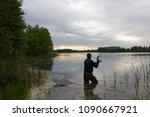 fisherman standing in the lake... | Shutterstock . vector #1090667921