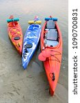Small photo of Three Traveling Kayaks on the Sand Beach near Beautiful River or Lake at the Evening. Travel, Adventure and Water Recreation Concept.