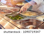 Stock photo chef standing behind full lunch service station with assortment of food in trays 1090719347
