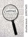"Small photo of Magnifying glass over contract document, highlighting the word ""contract."" Check that fine print!"