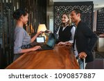 Couple and receptionist at counter in hotel. Check-in in hotel concept