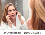 young  woman looking at mirror... | Shutterstock . vector #1091041367