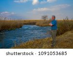 Small photo of Stern looking elderly unshaven man with grey hair standing with arms folded looking over a river image with copy space in landscape format