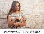 Stock photo favorite kitten girl is holding a red kitten little funny red cat biting fingers girl playfully 1091080085