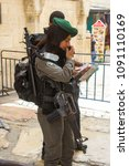 Small photo of 12 May 2018 Via Dolorosa Jerusalem Israel A young Israeli policeman and woman check a young couples identity papers just before the 70 year Independence celebrations.
