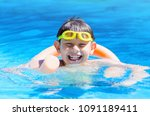 Small photo of Happy boy at the swimming pool with swimming goggles on head , floating with swim noodles on a summer day.