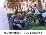 Small photo of man is sitting in a tourist tent and looks at the wath. Camping in forest, motorcycle touring, dual sport enduro, tent and off road adventure motorcycle, active life style concept
