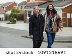 Small photo of Mid adult man and hiss mature father are laughing as they walk down the street together.