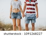 young couple holding hands at... | Shutterstock . vector #1091268227