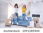 Small photo of Upsurge of emotions. Pleasant cheerful girls jumping happily in a new apartment while celebrating moving into a new shared flat together