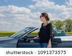 Attractive smiling young woman standing next  luxury convertible car.