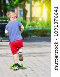 the boy skates on a scooter in... | Shutterstock . vector #1091376641