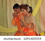 Small photo of Kampong Tom, Cambodia 04-10-2014. A Buddhist couple, in beautiful wedding clothes, kneel in ritual during the wedding ceremony, their hands together in a gesture of prayer and thanks.