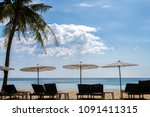 loungers and umbrella on beach... | Shutterstock . vector #1091411315