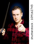 Small photo of Angry workman with a wood saw in hand pointing an accusatory finger at the camera as he snarls in frustration, conceptual of anger in the workplace, studio portrait on black
