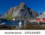 Picturesque fishing town of Reine on the coast of fjord on Lofoten islands in Norway - stock photo